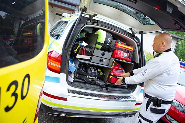 Ensihoitaja pakkaa välineitä ambulanssiin.