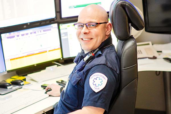 Taysin monivalvomopäivystäjä Harri Peltonen hymyilee työpisteessään valvomo- ja turvapalveluissa.