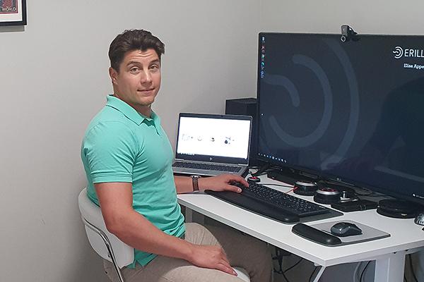 Atte Tuliainen istuu työpöytänsä ääressä.