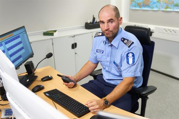 Komisario Patrik Karlsson työpöydän ääressä Helsingin poliisilaitoksen johtokeskuksessa Pasilassa.