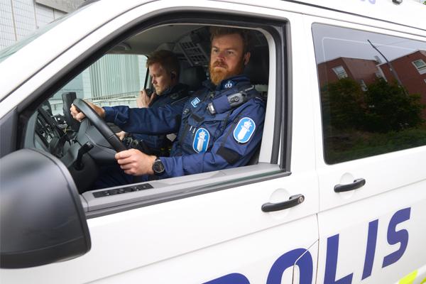 Virkapukuiset poliisit istuvat partioautossa.