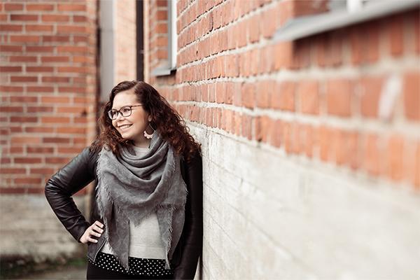 Reetta Siltasalmi-Kautto hymyilee ja nojaa seinään.
